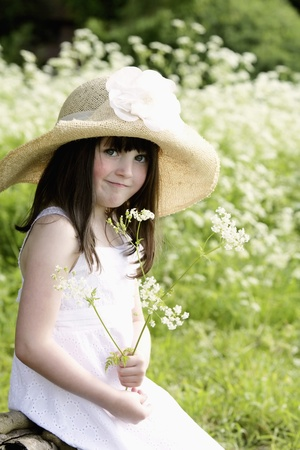 Girl in meadow holding flower Stock Photo - 8458524