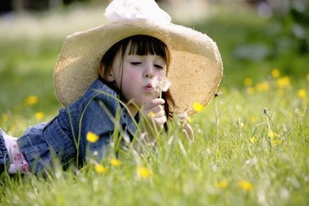 Girl blowing dandelion in the meadow photo