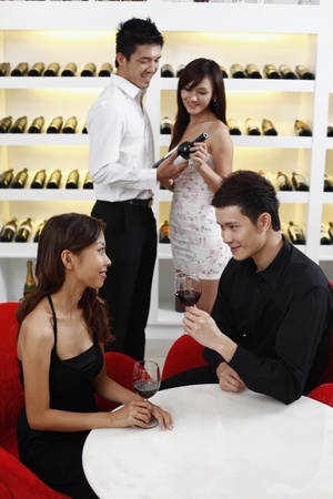 Young couple enjoying wine, another couple choosing wine in the background photo