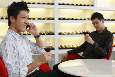 Men enjoying wine, another man is talking on the phone photo