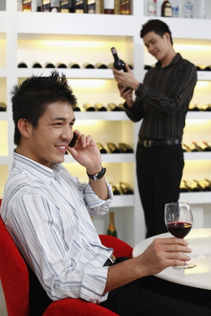 Man talking on the phone, another man is choosing wine in the background photo