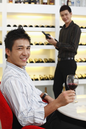Man holding a glass of wine, another man is choosing wine photo