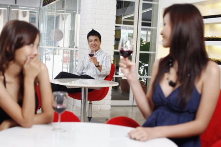 Man flirting with woman sitting at another table photo