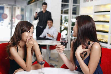 Men flirting with women sitting at another table photo