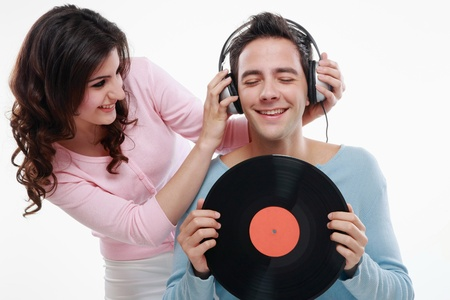 Man listening to music, woman pulling man's headphones Stock Photo - 8536396