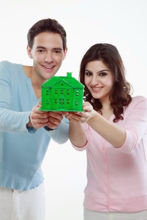 Man and woman holding a green house  photo