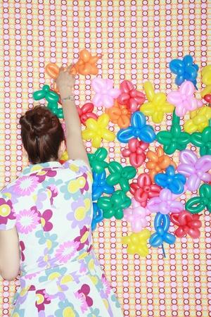 sculpted: Vrouw versieren de muur met gebeeldhouwde ballonnen