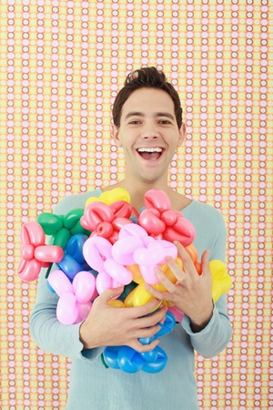 armful: Man with an armful of sculpted balloons