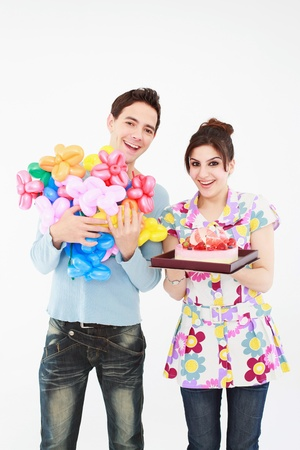 sculpted: Woman holding cake while man holding sculpted balloons Stock Photo