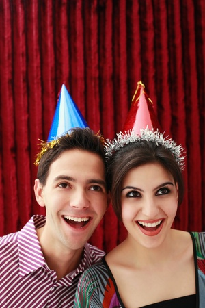 Man and woman with party hats smiling while looking up photo