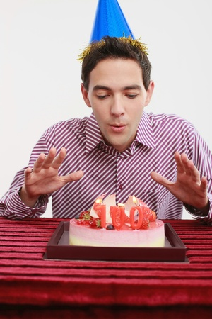 Man blowing candles on birthday cake Stock Photo - 8536690