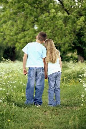 girl bonding: Boy and girl holding hands in the park Stock Photo