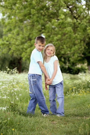 Boy and girl holding hands in the park Stock Photo - 8536279