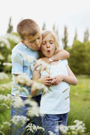 Boy and girl blowing dandelion together photo