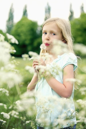 Girl playing with dandelion photo