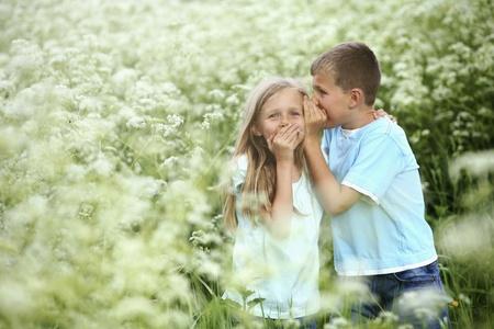 Boy whispering into girls ear, girl giggling photo