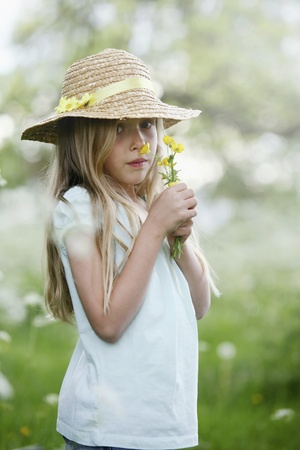 Girl with straw hat smelling flowers photo