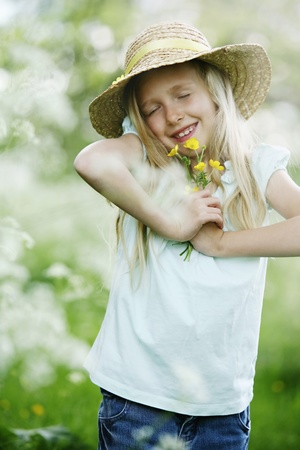 Girl with straw hat holding flowers photo