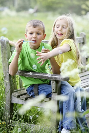 Boy and girl playing with soap bubbles photo
