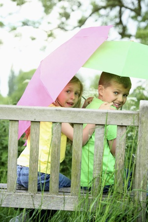 Boy and girl sitting on a bench hodlign umbrellas photo