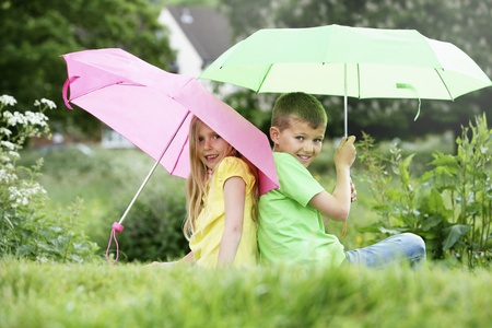 Boy and girl sitting on field holding umbrellas Stock Photo - 8536580