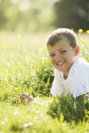 lying forward: Boy lying forward on the field smiling