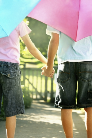 only boys: Boy and girl with umbrellas holding hands