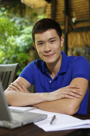 revising: Man smiling with laptop on the table