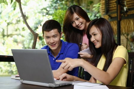 using the laptop: Man and women studying together Stock Photo