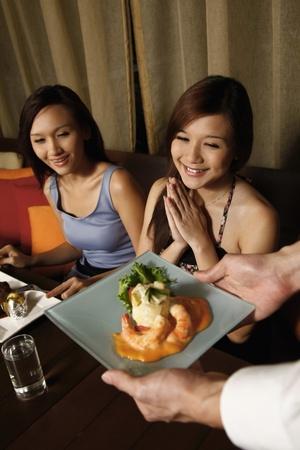 Camarero servir alimentos a las mujeres