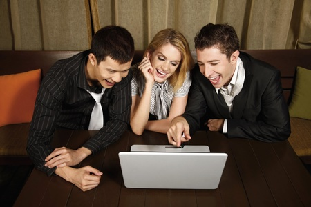 Happy business people looking at laptop Stock Photo - 8536637