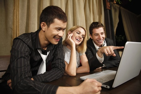Happy business people looking at laptop Stock Photo - 8536850