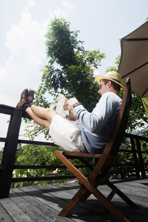 southern european descent: Man sitting with his feet up while reading magazine