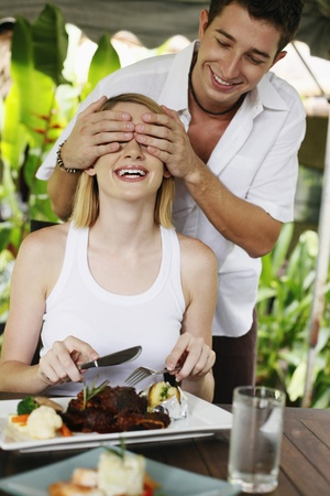 Man covering womans eyes photo
