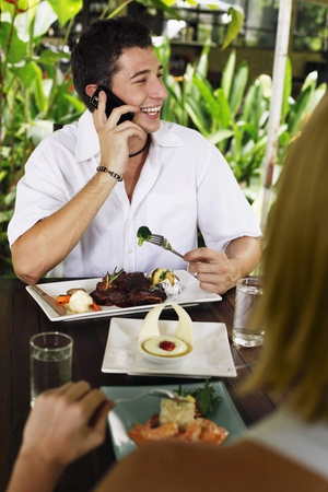 Man and woman eating at a cafe, man talking on the phone Stock Photo - 8536615