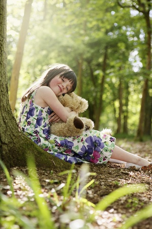 Girl hugging her teddy bear photo