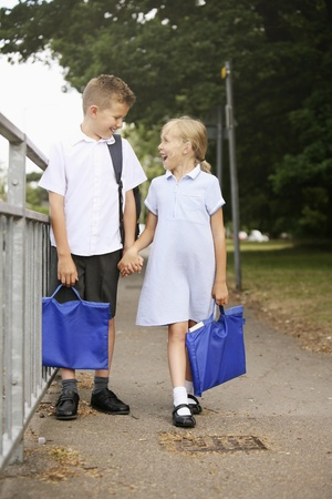 Boy and girl walking home from school photo