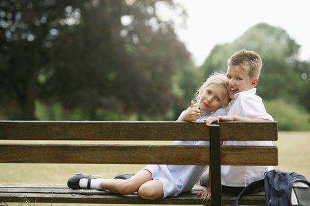 innocence: Boy and girl sitting on bench