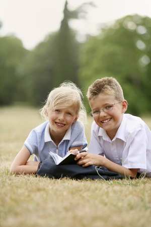 Boy and girl studying together in the park photo