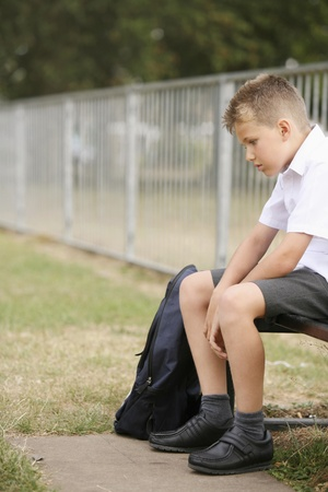exhaustion: Boy sitting on a bench contemplating