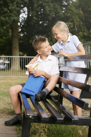 Boy sitting on bench holding sandwich, girl smiling at him photo
