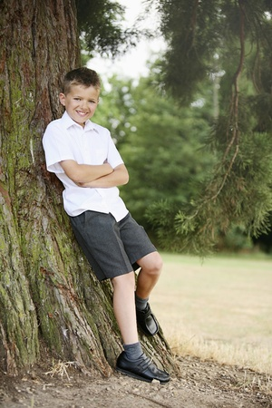 Boy leaning against tree with his arms folded Stock Photo - 8606210