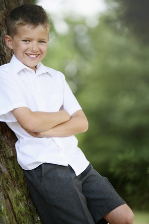 Boy leaning against tree with his arms folded