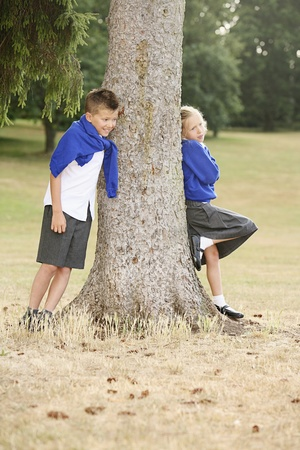 Boy and girl leaning against tree photo