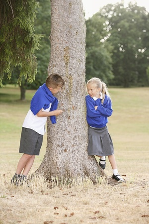 Boy and girl talking beside a tree photo