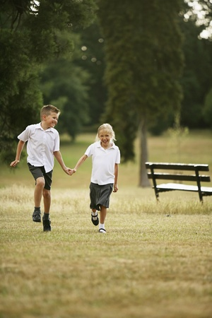 Boy and girl holding hands while running in the park photo