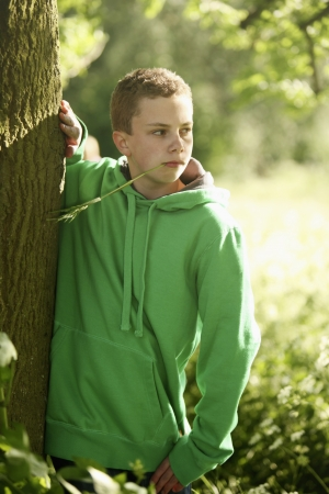 Boy standing next to a tree and looking away photo
