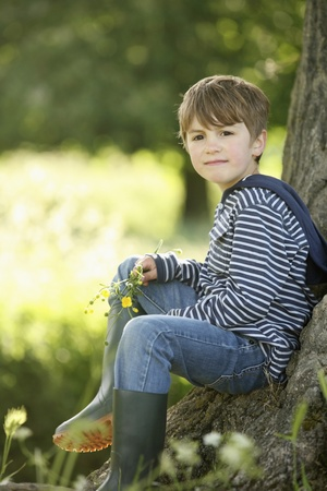 Boy sitting on bark of a tree photo