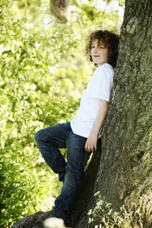 Boy leaning against a tree photo