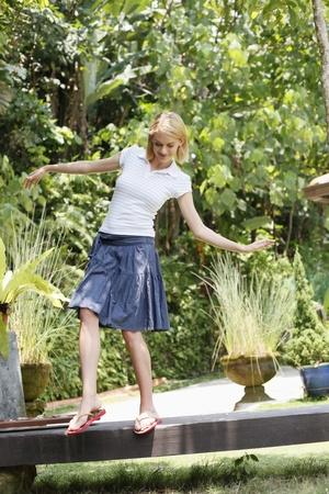 Woman balancing herself on a footbridge Stock Photo - 8606209